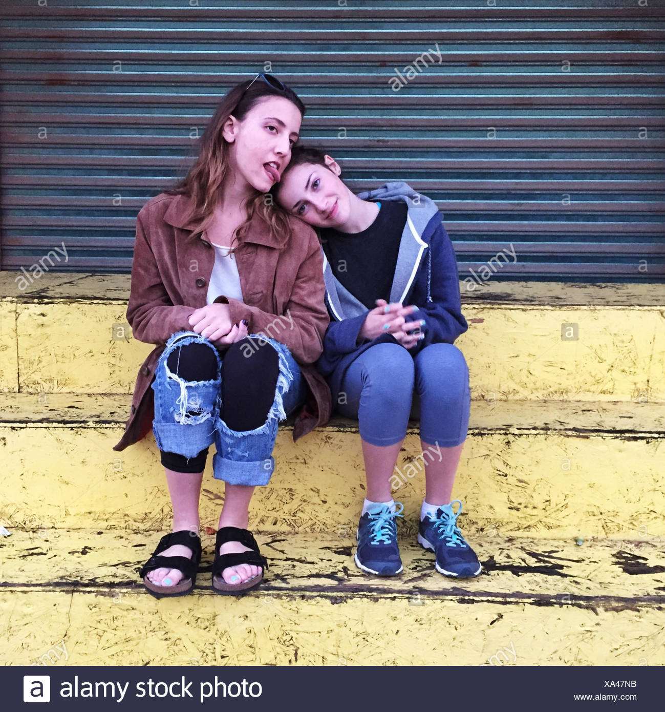 Two girls sitting on a step, messing about - Stock Image