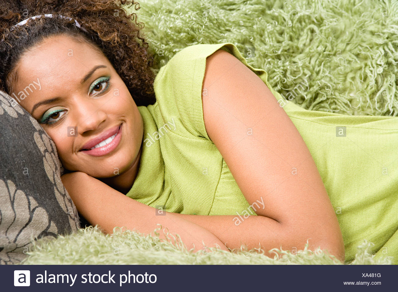 Woman reclining on arm chair Stock Photo