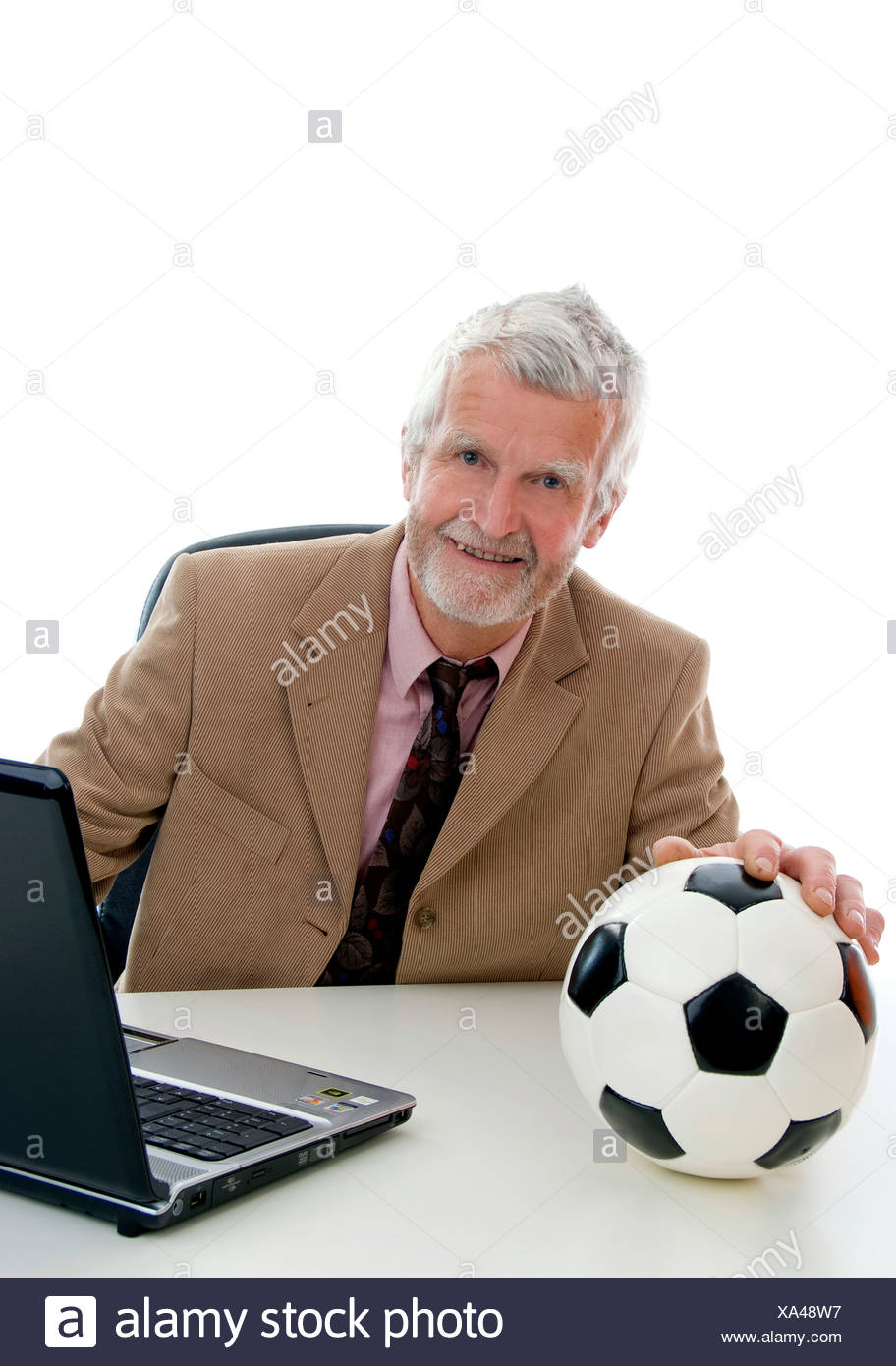 elder retiree with football and laptop - Stock Image