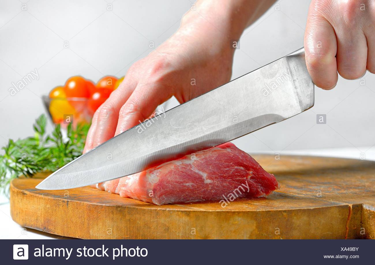 Stainless steel butcher knife cut meat. - Stock Image