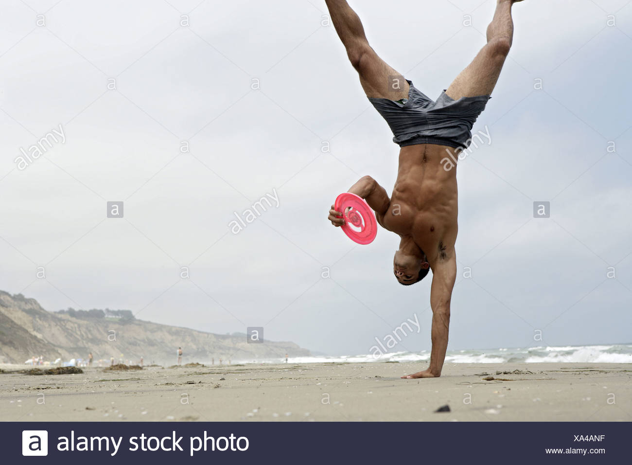 A person performs gymnastic on a beach. Stock Photo