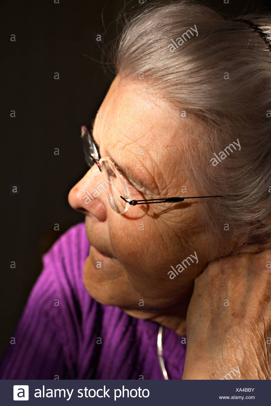 Close-up profile of an elderly woman wearing glasses as she looks away over black background - Stock Image