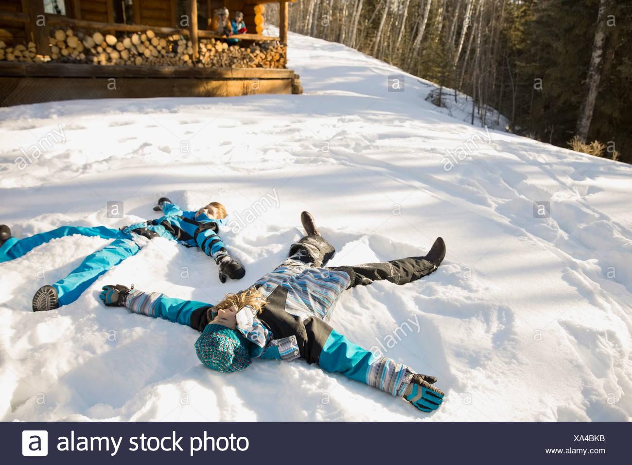 Siblings making snow angels - Stock Image