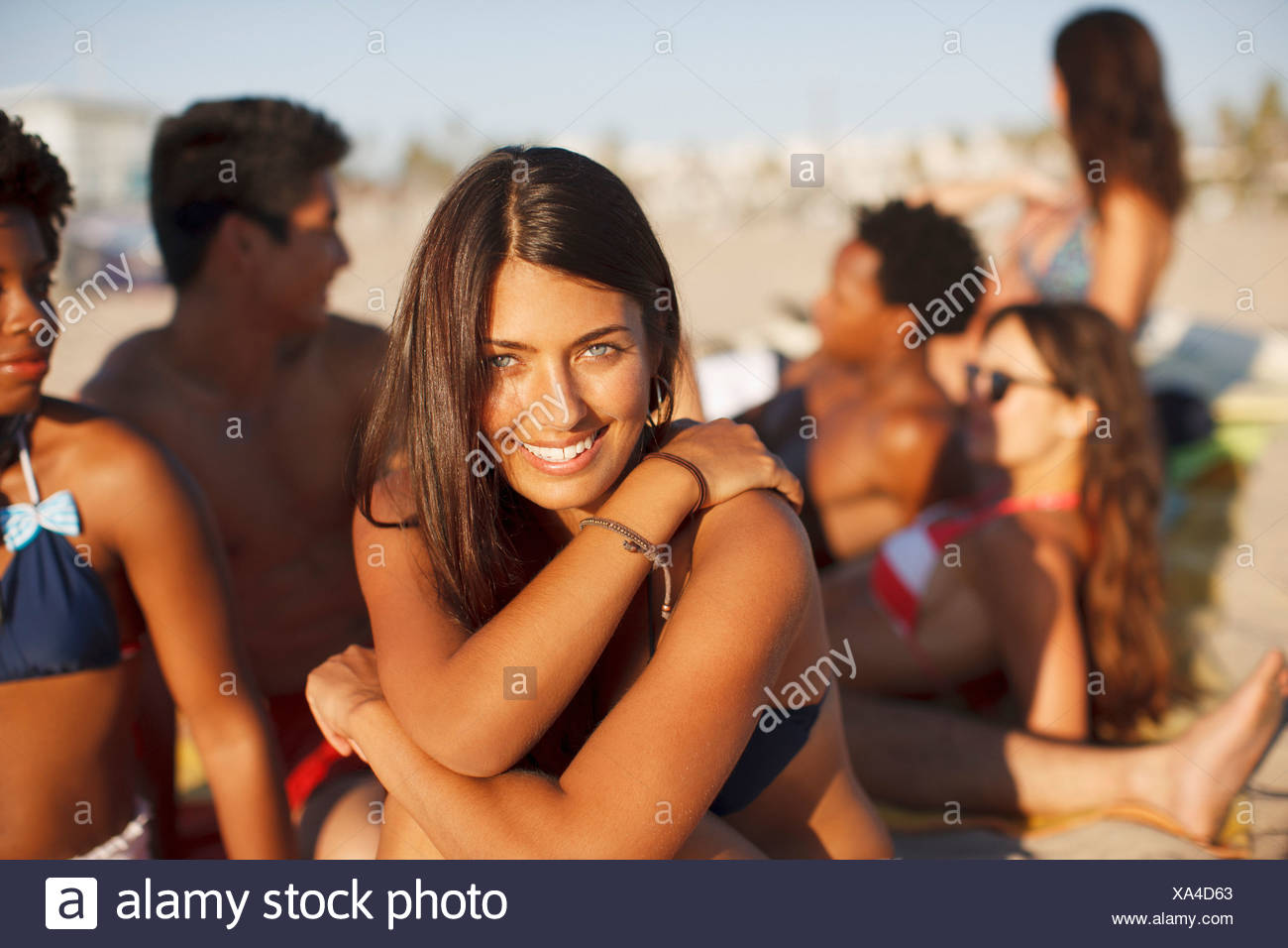 Woman sitting with friends on beach - Stock Image