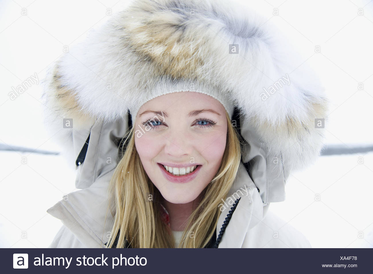 A portrait of a young woman wearing a fur trimmed hooded jacket - Stock Image