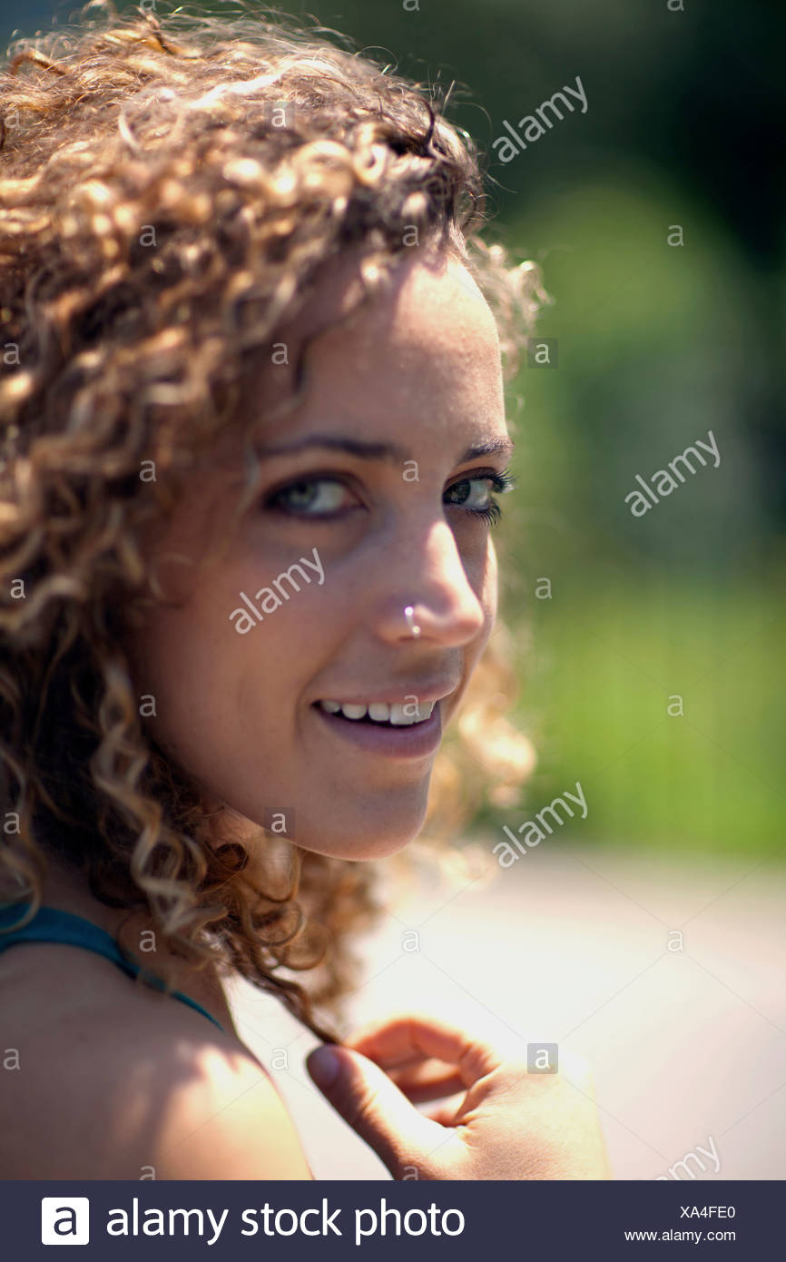 Woman with curly hair and nose ring, close up Stock Photo