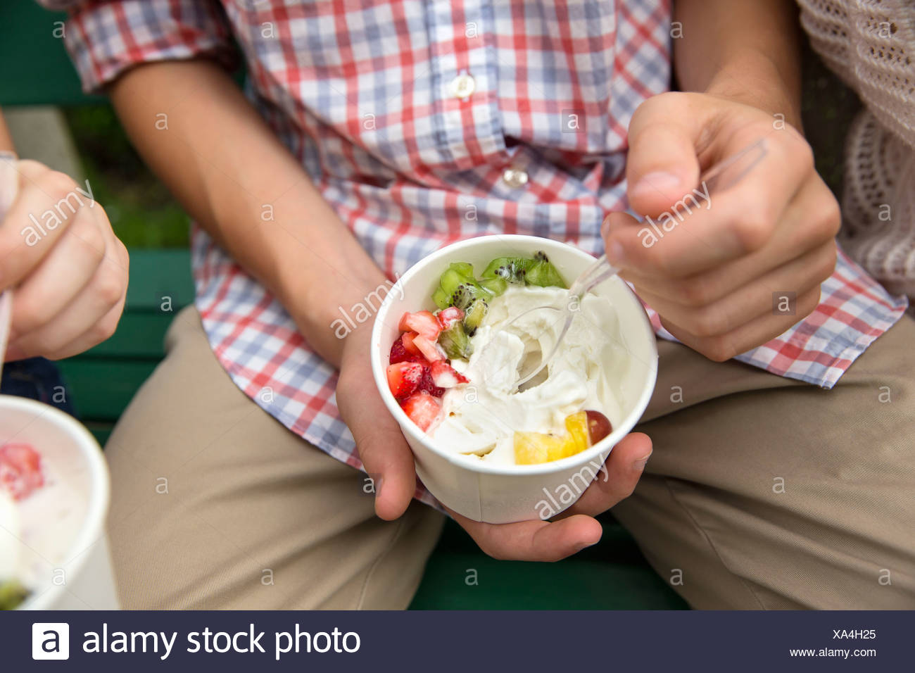 Young people sitting side by side, eating fresh organic fruit and yoghurt desert. Stock Photo