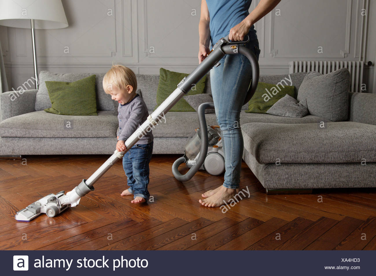 Laughing toddler helping his mother hoovering wooden floor - Stock Image