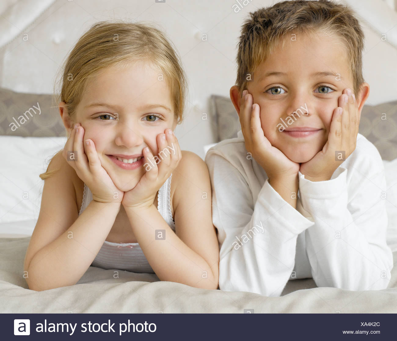 Two young kids lying on their stomachs smiling - Stock Image