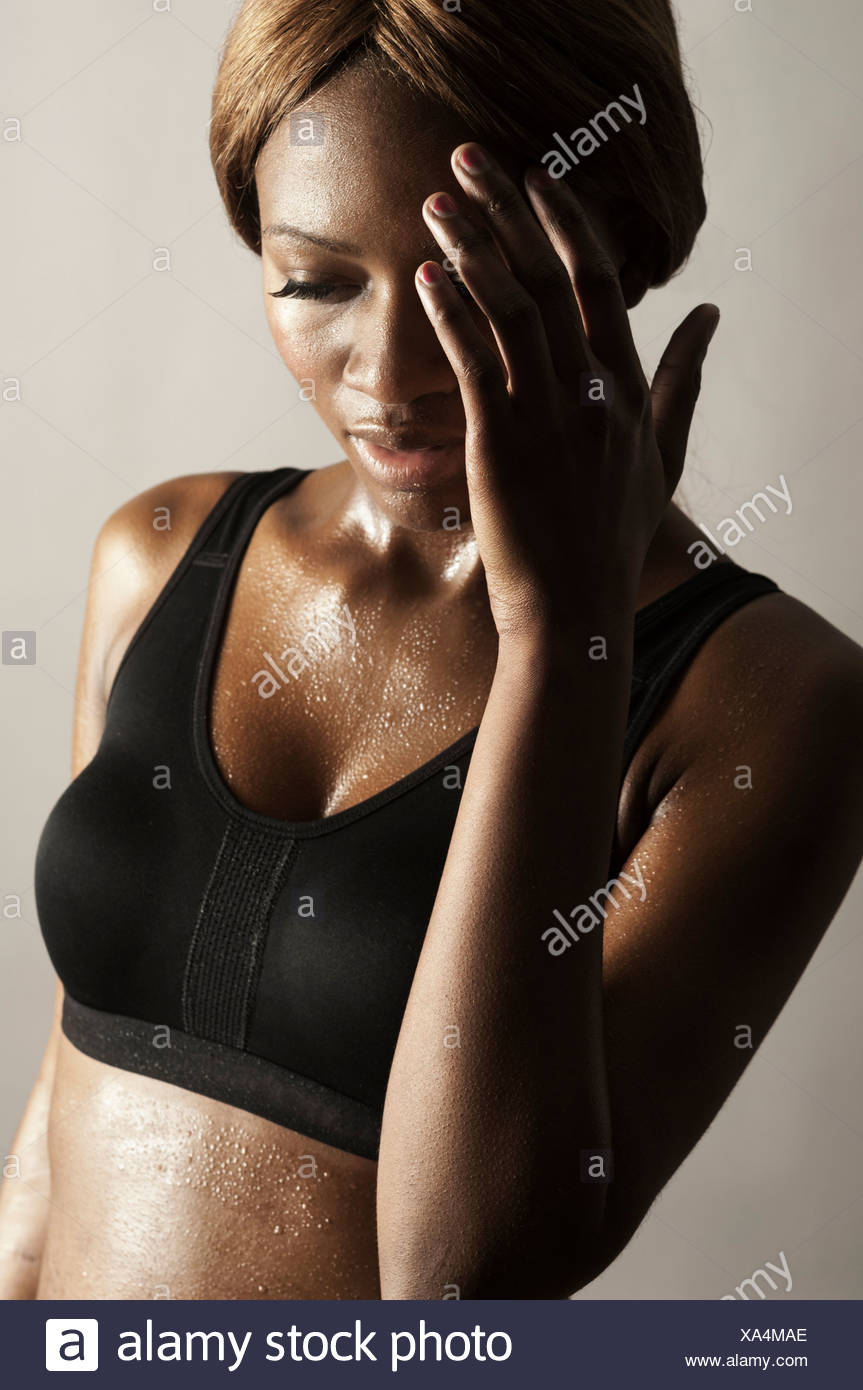 Studio shot of woman with hand on face - Stock Image