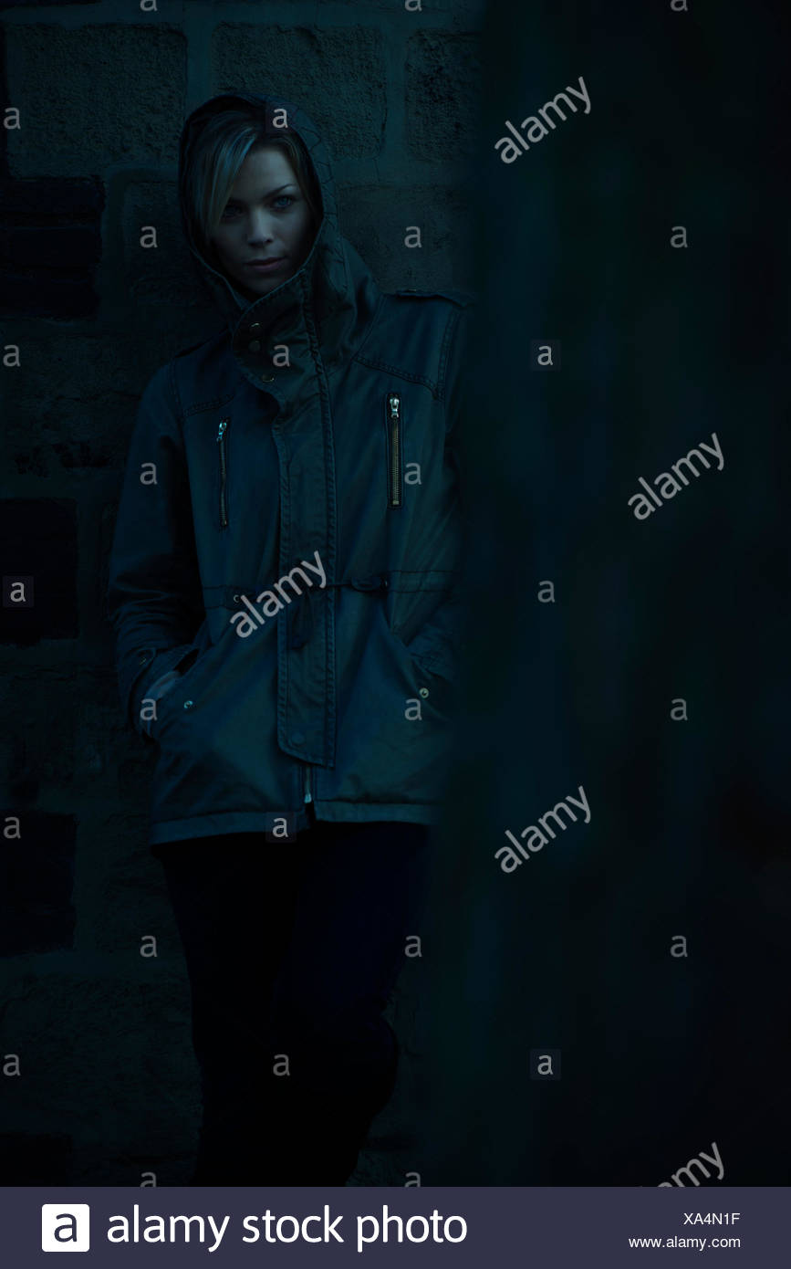 Woman wearing hooded jacke, leaning against wall outdoors - Stock Image
