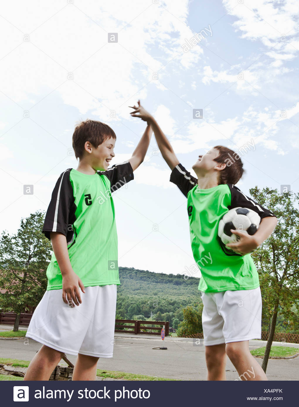 Twin brothers high five - Stock Image