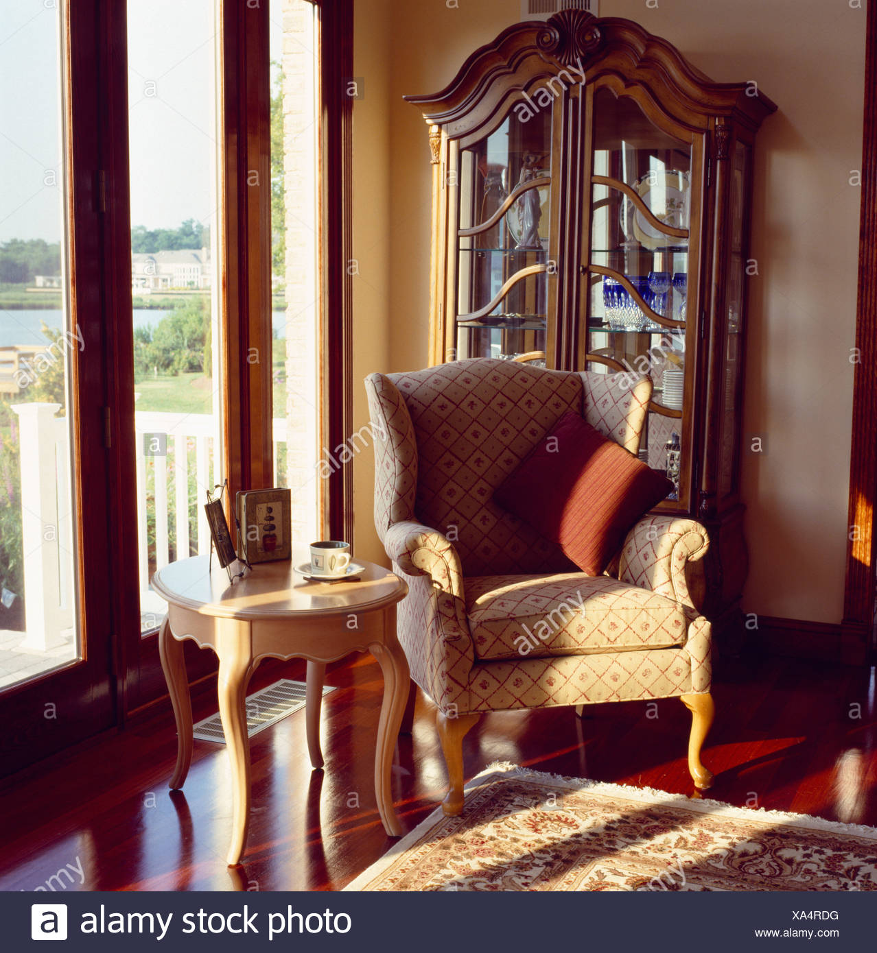 Neutral Patterned Armchair In Front Of Antique Glass Fronted