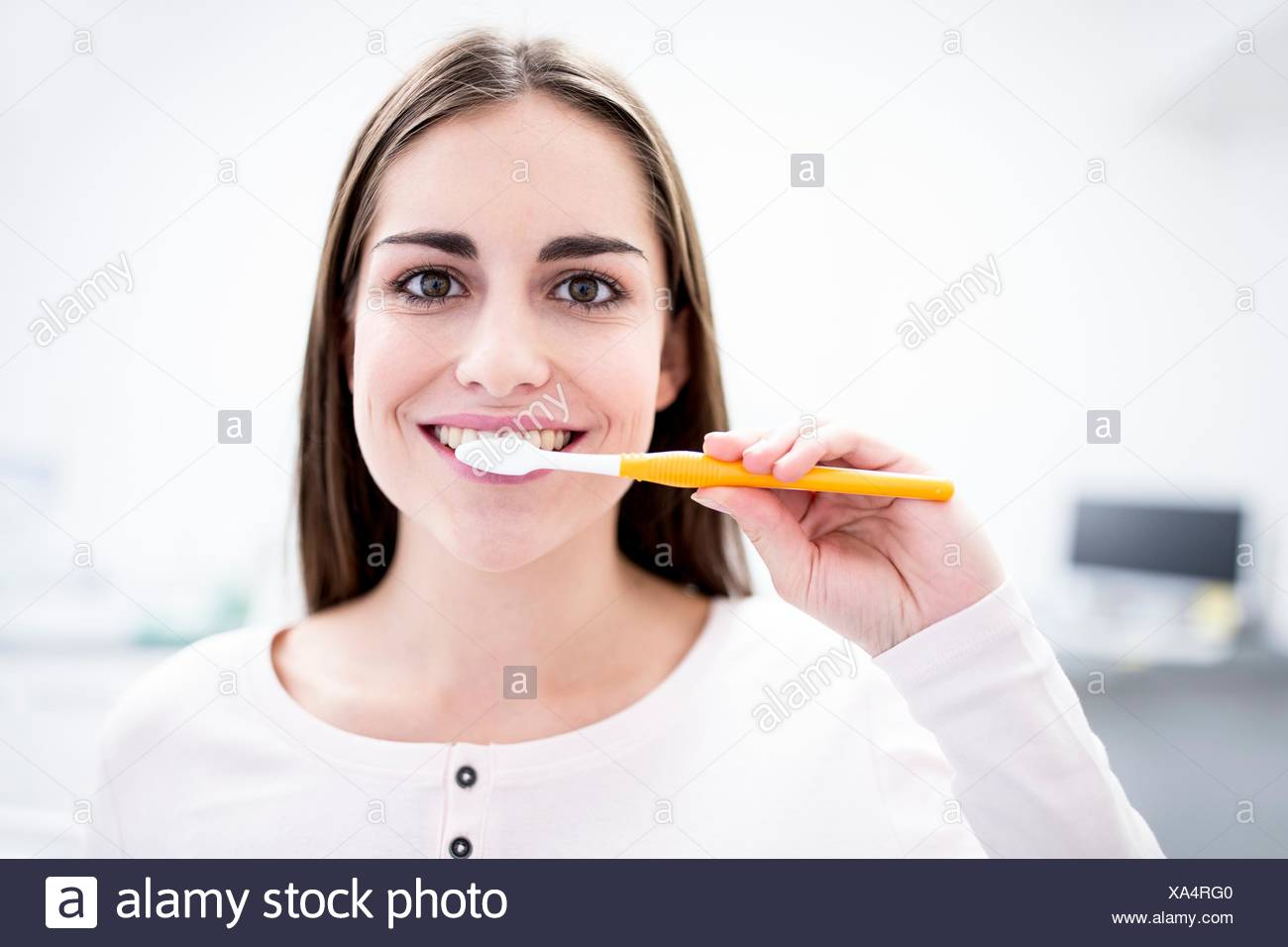 MODEL RELEASED. Young woman brushing teeth, portrait, close-up. - Stock Image