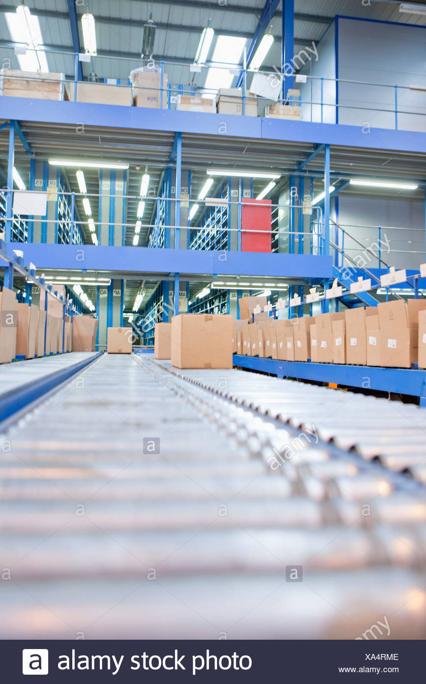 Boxes on conveyor belts in distribution warehouse - Stock Image