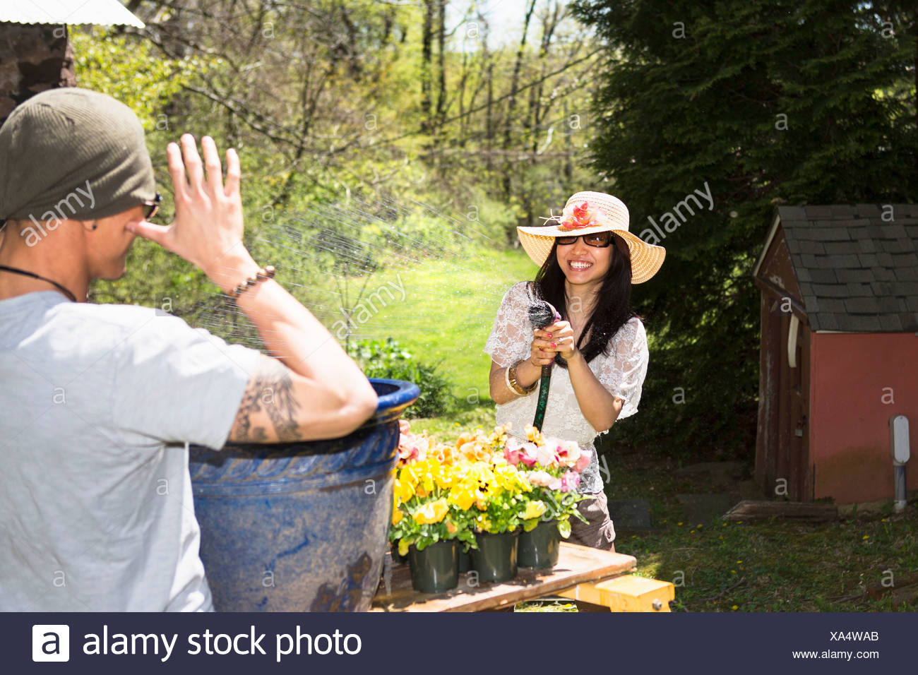 Woman spraying man with hosepipe - Stock Image