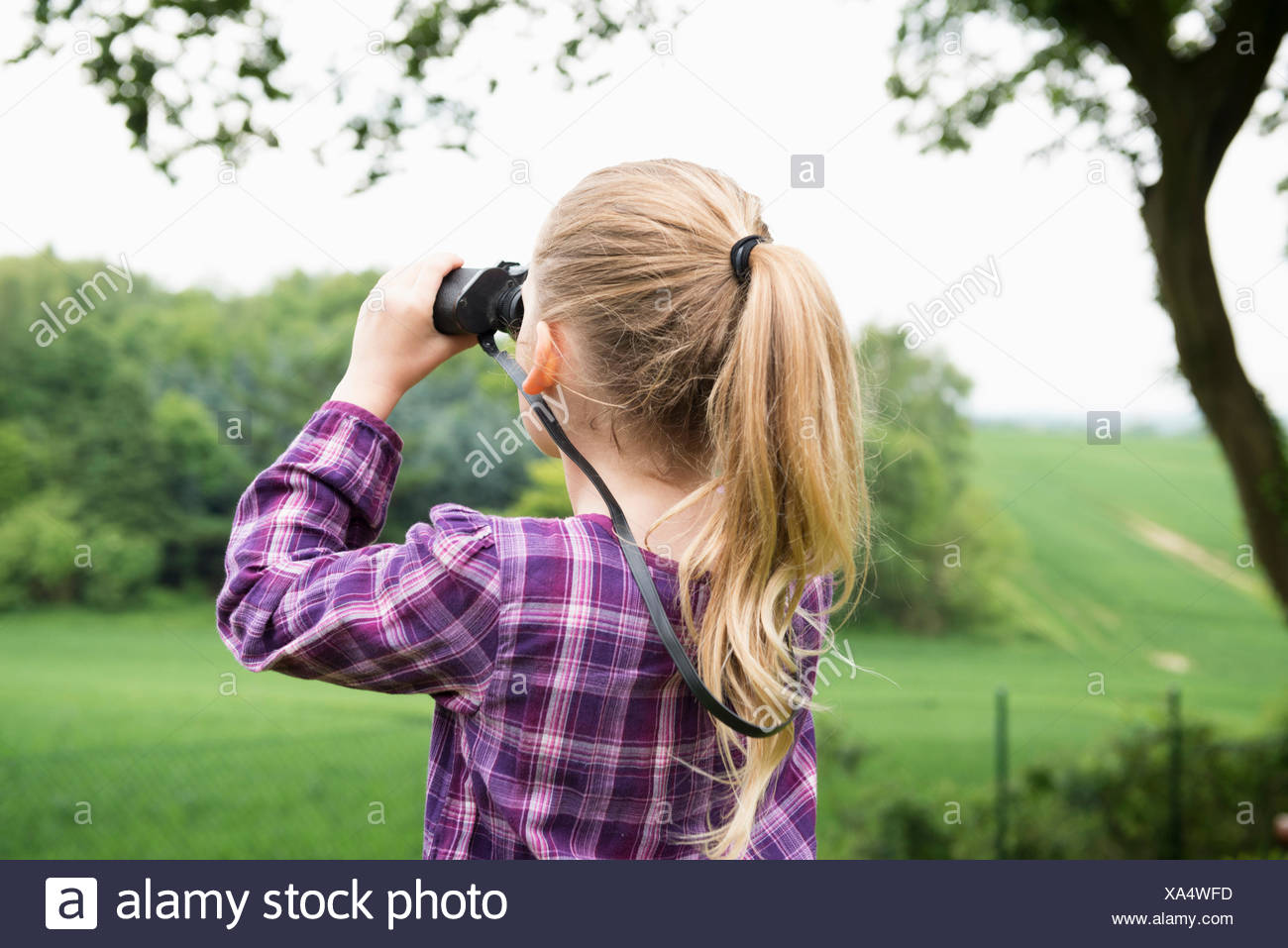 Girl using binoculars - Stock Image