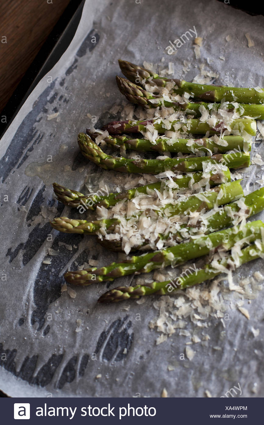 Fresh green asparagus sprinkled with grated Parmesan cheese before roasting - Stock Image