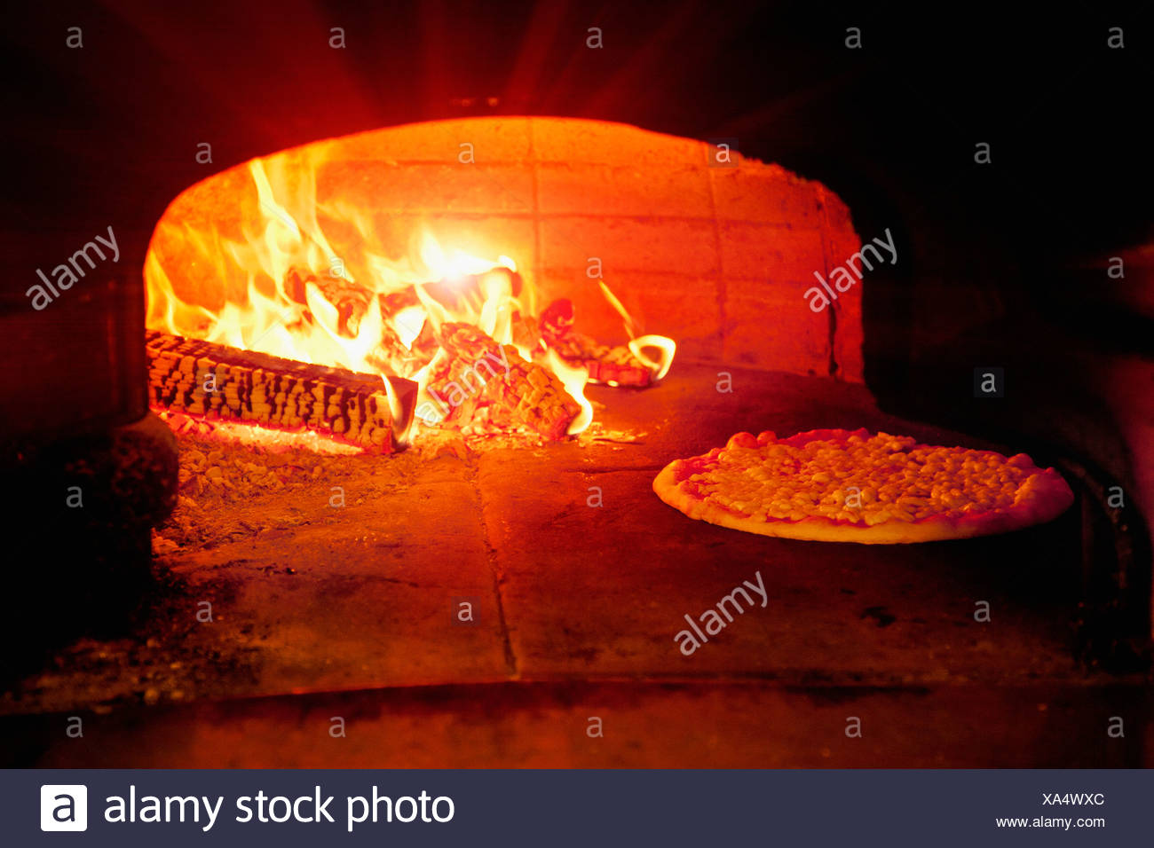 Pizza baking in wood burning oven - Stock Image