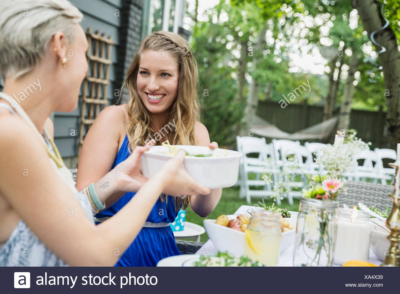 Smiling women passing food at garden party lunch - Stock Image