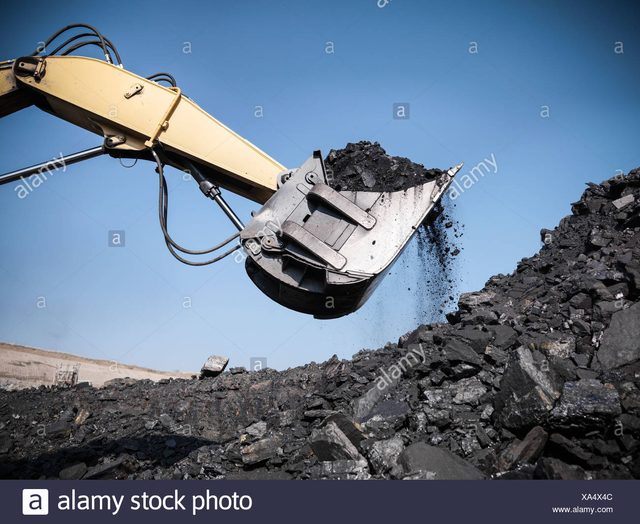 Digger scooping coal at mine - Stock Image