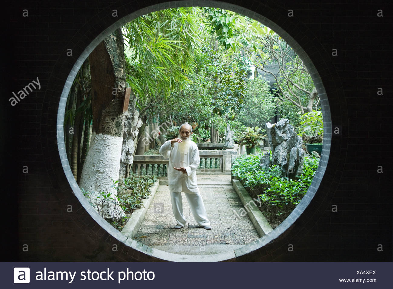 Elderly man wearing traditional Chinese clothing doing Tai Chi - Stock Image