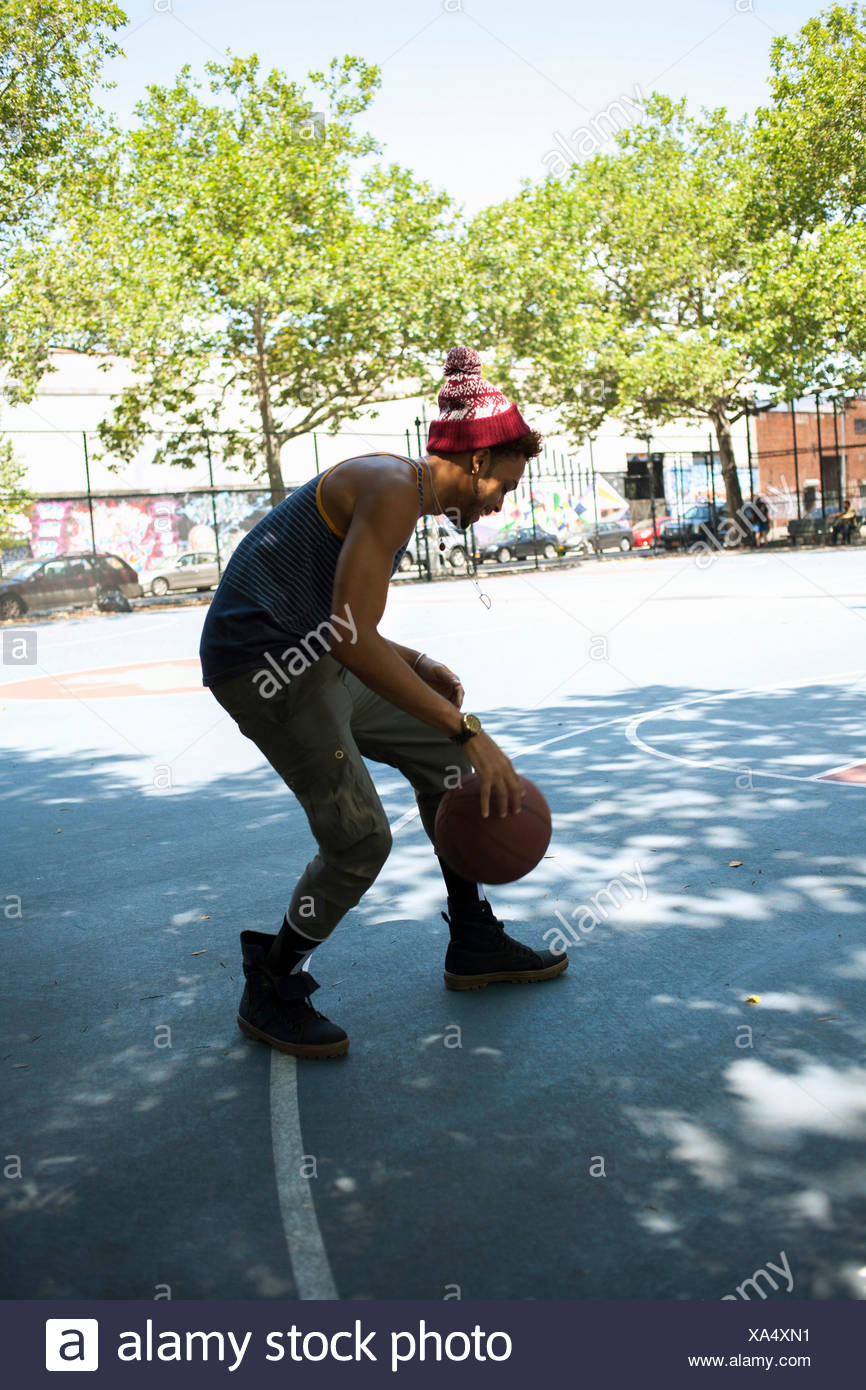 Young man dribbling basketball on outdoor court - Stock Image