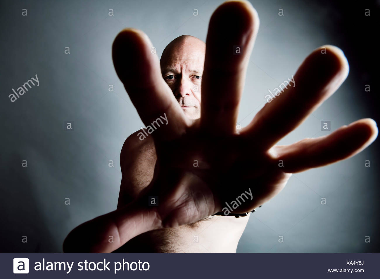 Man defending viewer with his hand - Stock Image