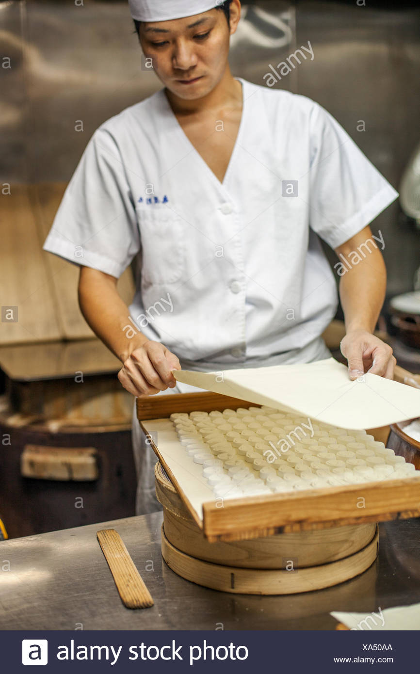 A small artisan producer sweets called wagashi. a chef covering a tray of small moulded sweets for drying. - Stock Image