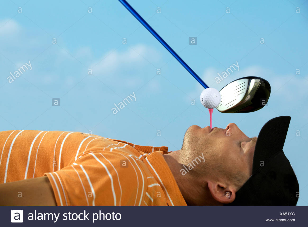 Man balancing golf ball on tee in his mouth - Stock Image