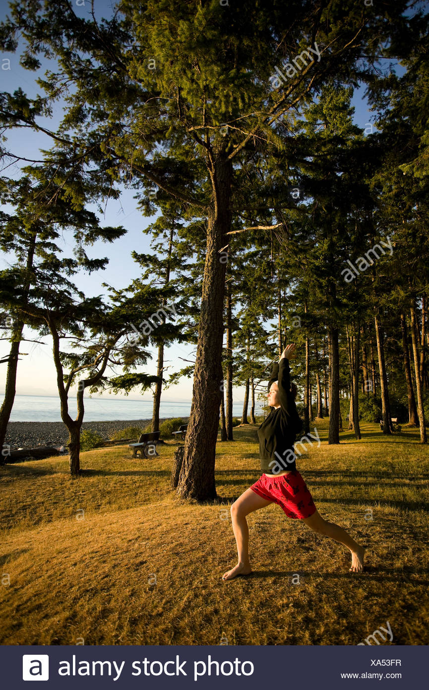 A womanduring a yoga pose at Kitty Coleman Beach campground.  Courtenay Comox Valley Vancouver Island British Columbia Canada. - Stock Image