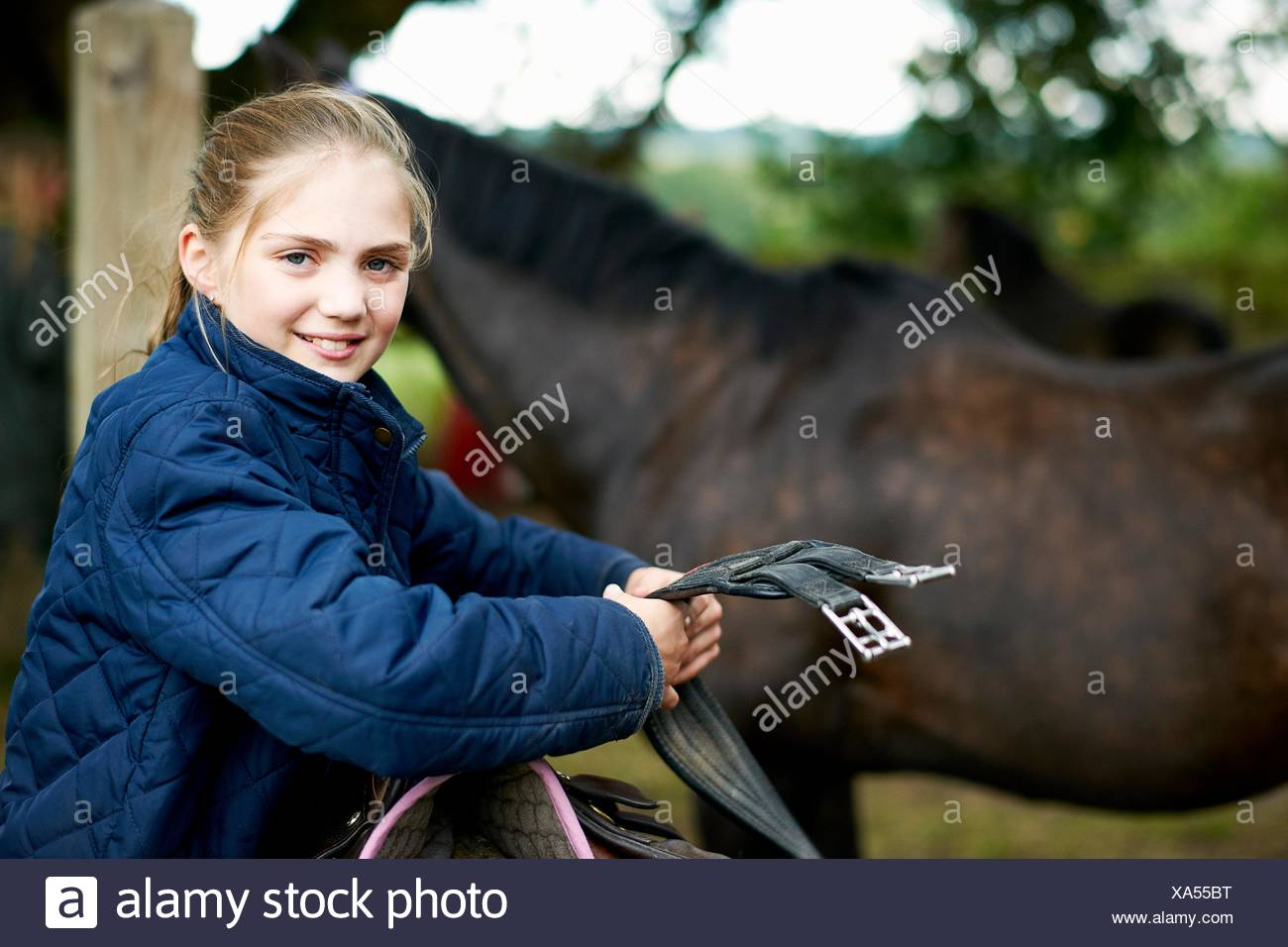 Girl horseback rider preparing saddle - Stock Image
