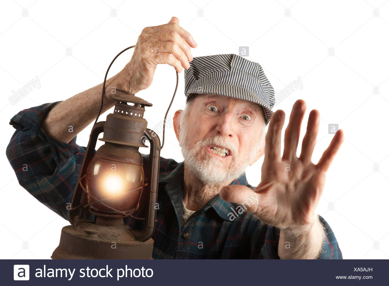 Apprehensive railroad man holding a glowing red lantern. - Stock Image