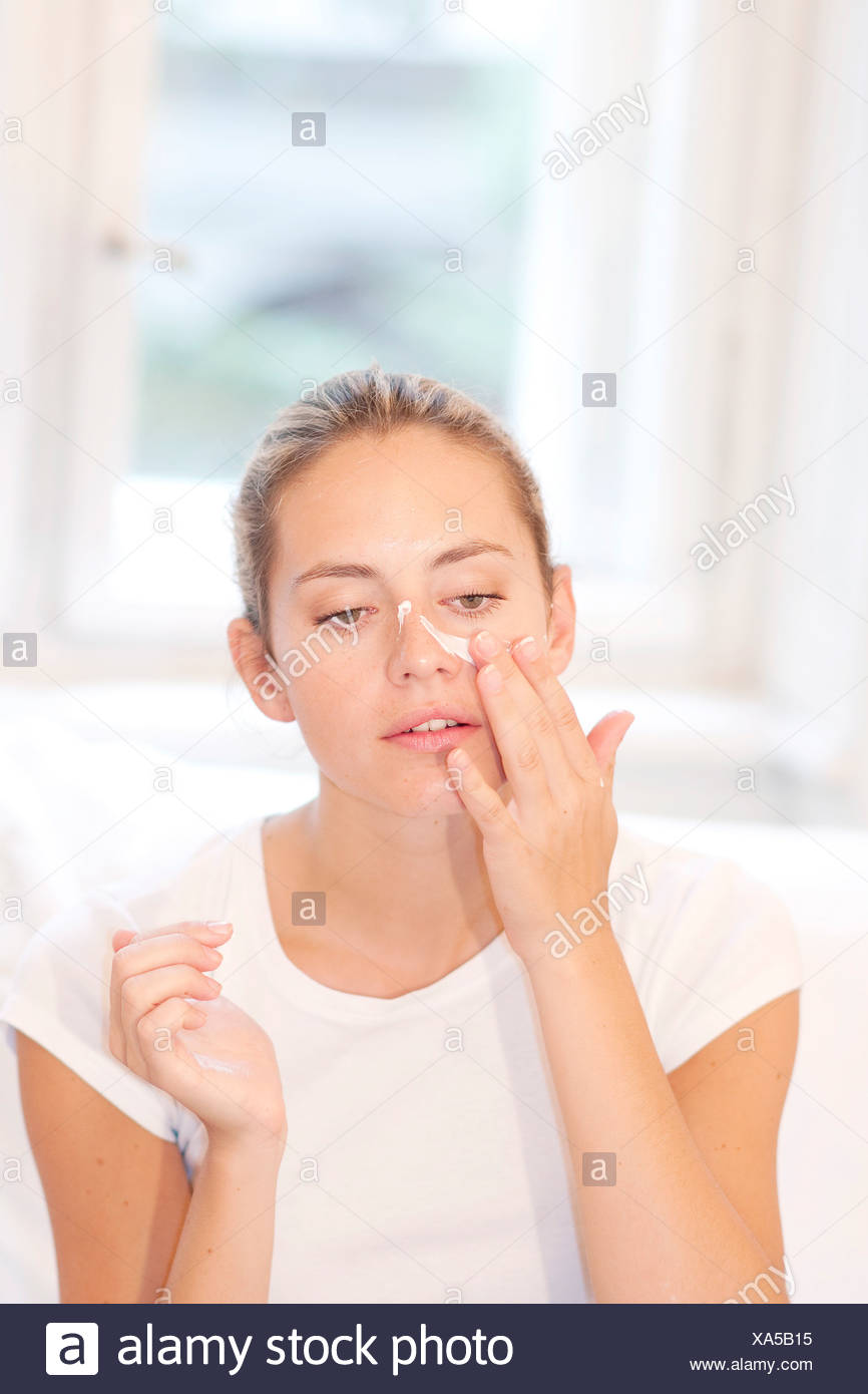 Female highlighted fair hair off her face, wearing a white t shirt, applying face cream to her nose, unsmiling, looking down - Stock Image