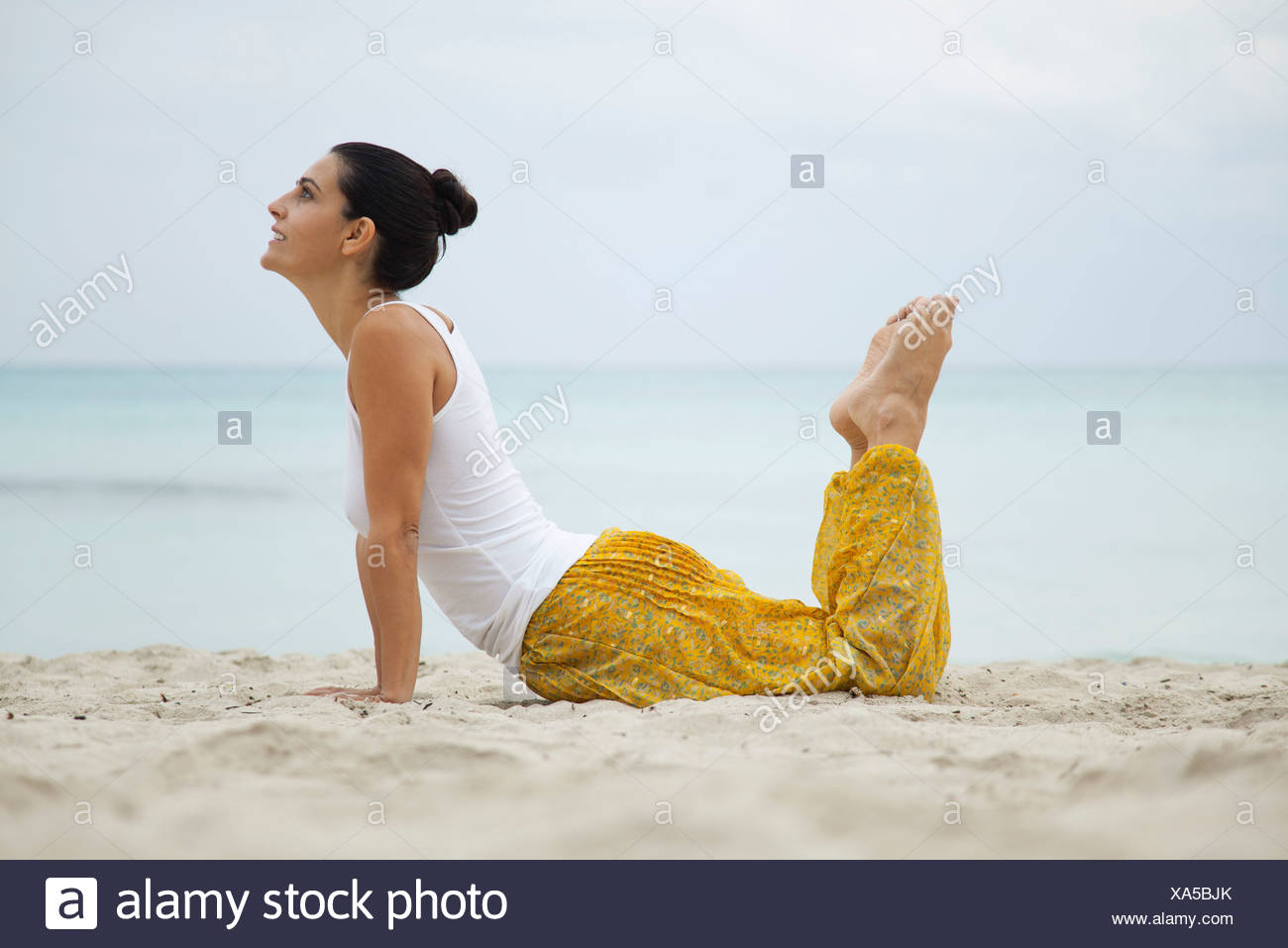 Mature woman practicing yoga on beach, side view - Stock Image