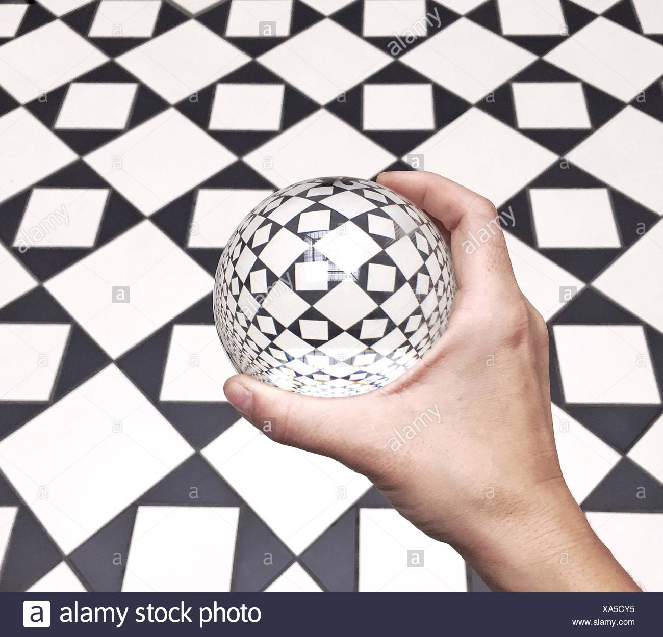 Close-Up Of Hand Holding Ball Against Chequered Floor - Stock Image