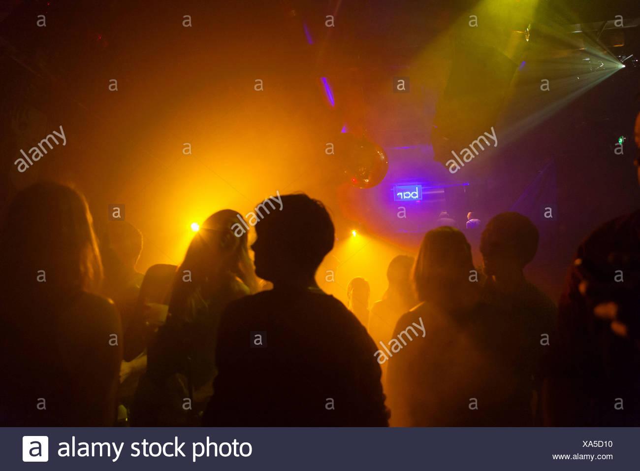 Nightclub scene with people dancing, disco ball, lighting equipment - Stock Image
