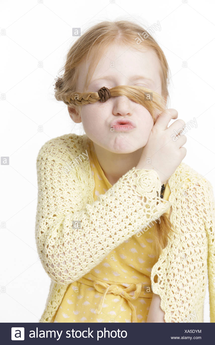 Girl, 8, making a face and holding a braid in front of her eyes Stock Photo