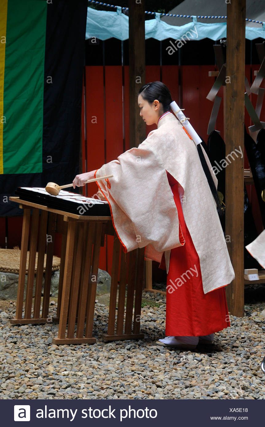 Shrine maiden dividing the holy sake, rice wine, which every participant of the procession from the Shimogamo shrine to the Mik - Stock Image
