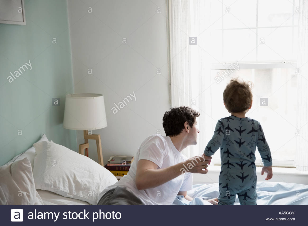 Father and son in pajamas looking out window - Stock Image