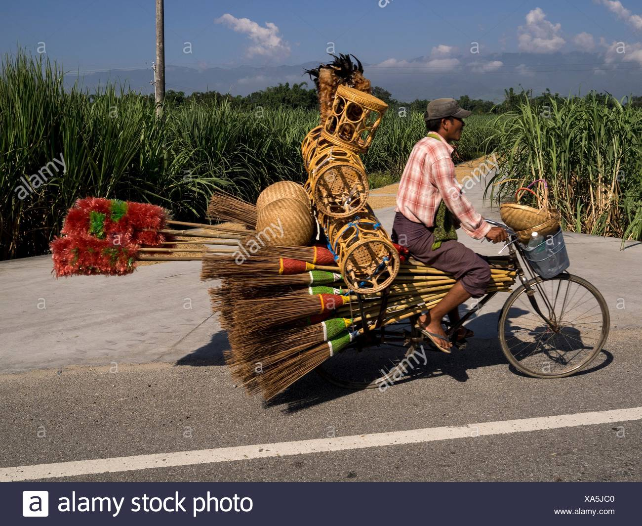 A vendor rides his bicycle laden with brooms, stools, brushes and baskets. - Stock Image