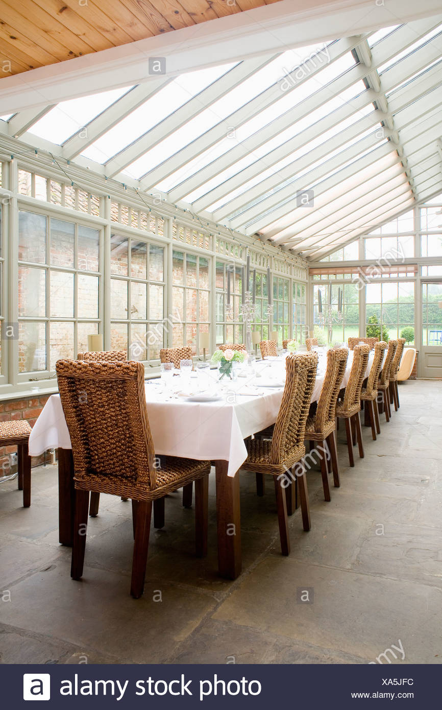 High Back Wicker Chairs And Table With White Linen Cloth In Conservatory  Dining Room With Flagstone Floor