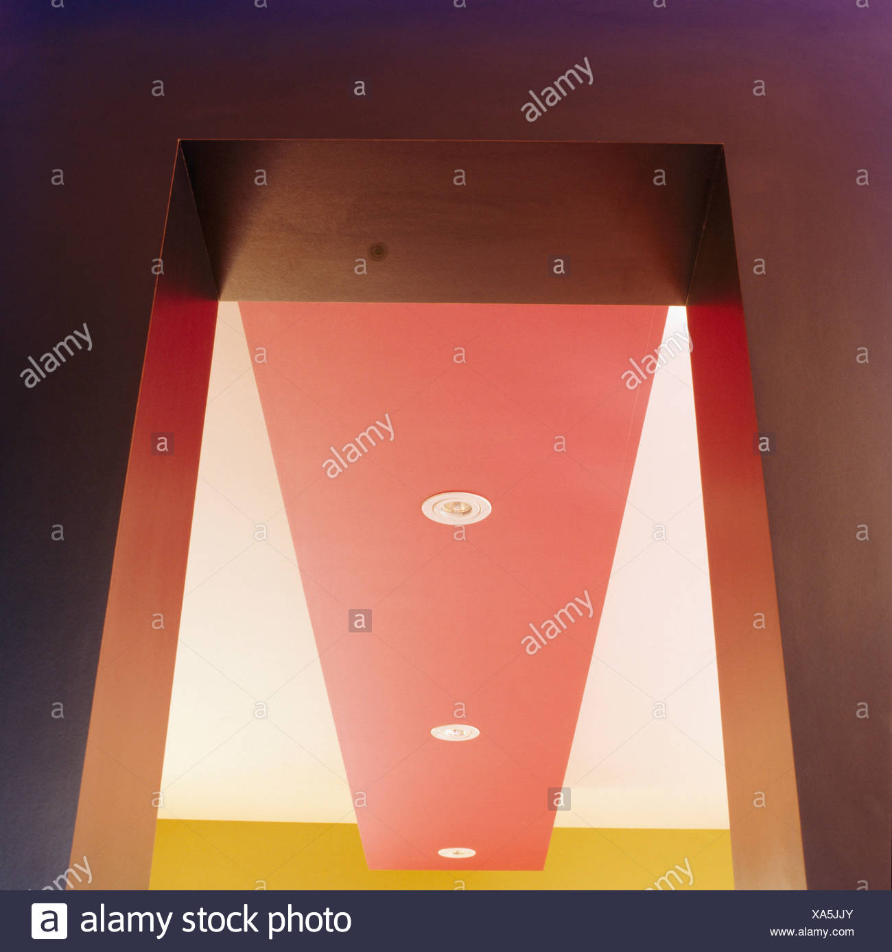 Upward close-up view of modern red and white ceiling with recessed lighting - Stock Image