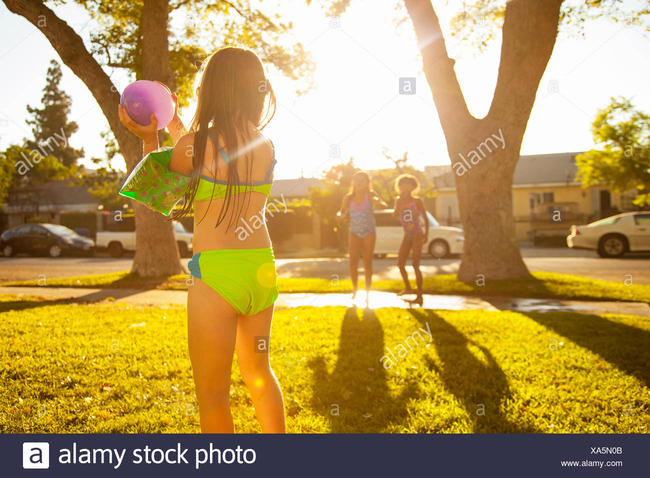 Girl chasing friends with water balloon in garden - Stock Image