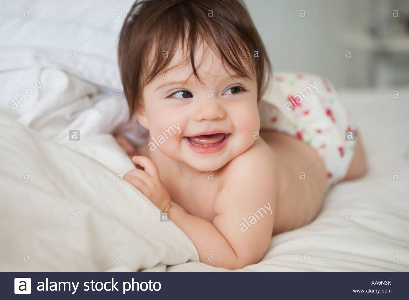 Baby girl laying in bedsheets Stock Photo