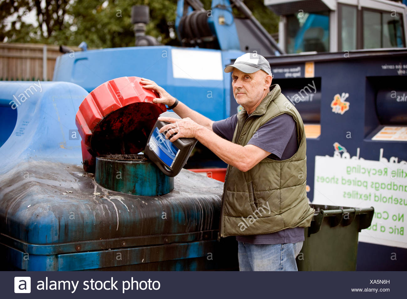 A senior man pouring oil into a recycling container - Stock Image