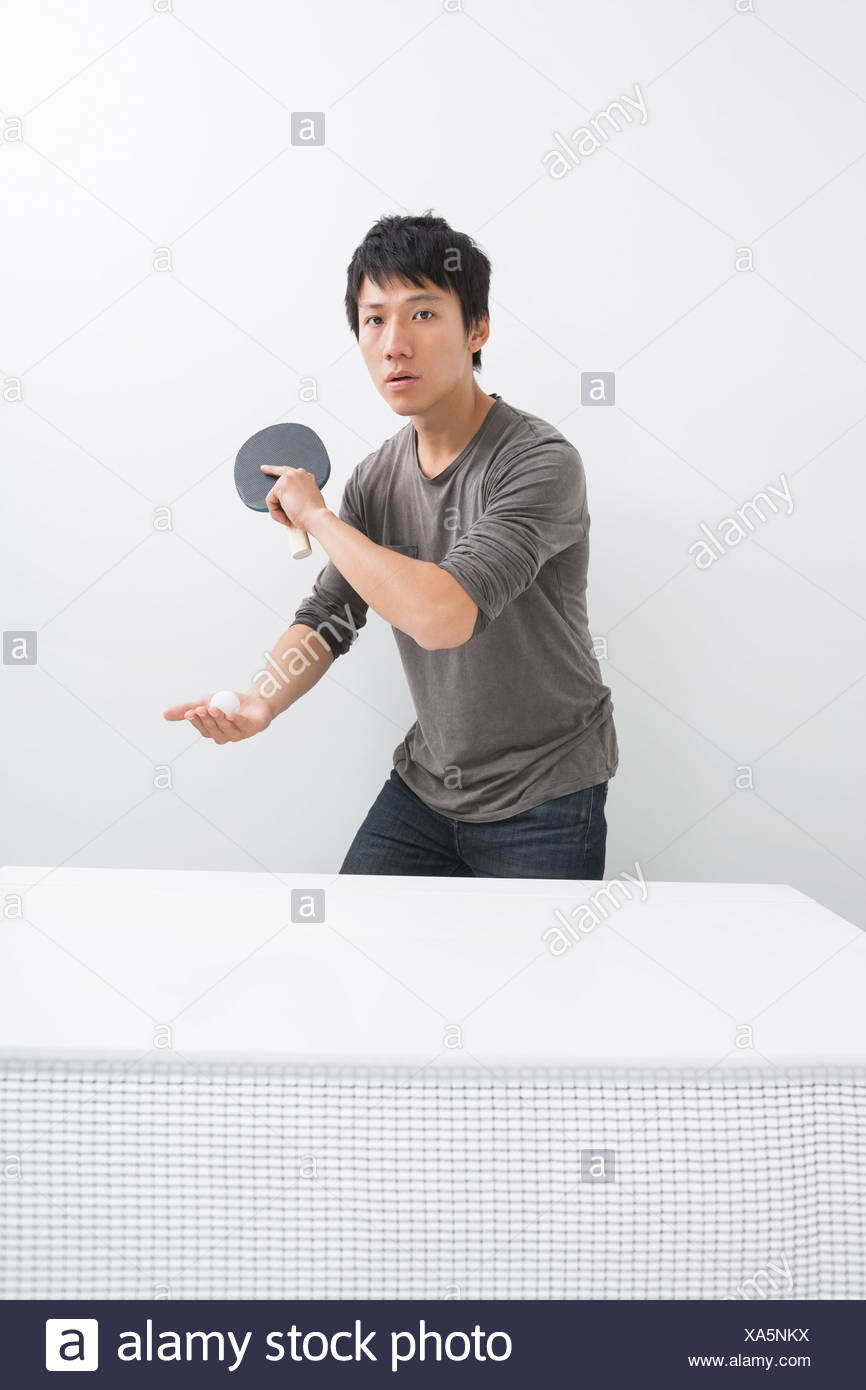 Portrait of Asian mid adult man playing table tennis - Stock Image