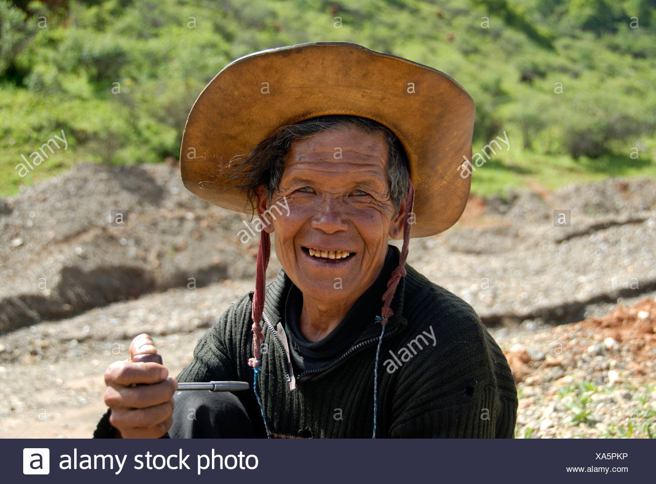 Portrait, ethnology, man of the Mosu ethnicity with hat, smiling and smoking a pipe, Yongning, Lugu Hu Lake area, Yunnan Provin - Stock Image