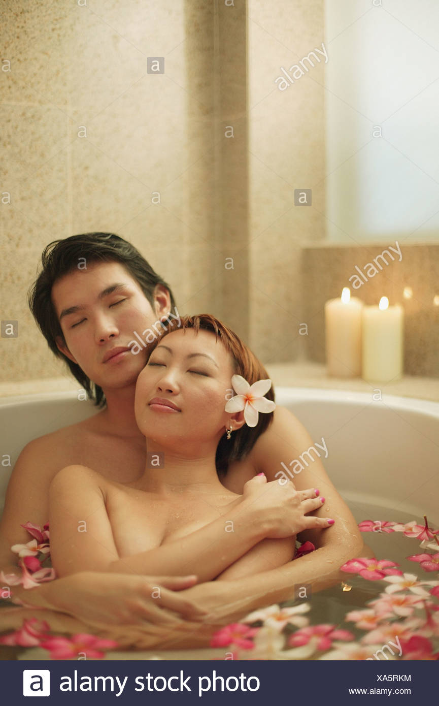 Couple hugging in tub, flowers floating around - Stock Image