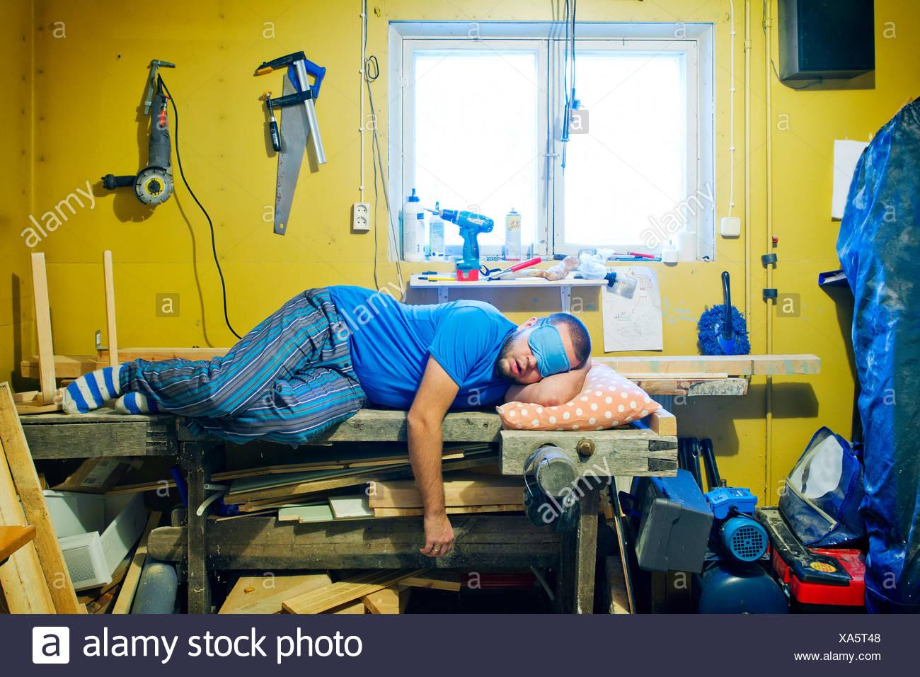 Man sleeping on workshop's table - Stock Image